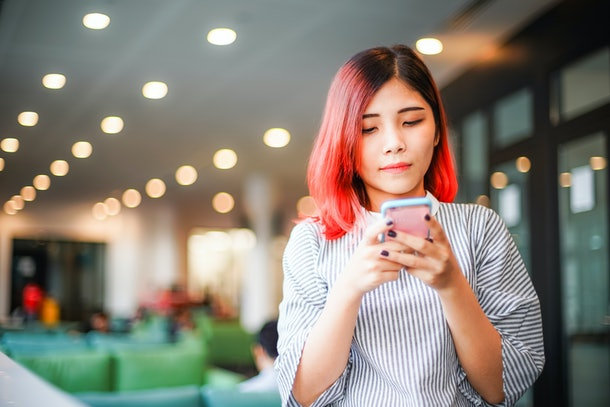 Portrait of charming, pretty, positive, sweet, stylish, lovely, modern girl having smart phone in hands, chatting with friends, checking email, using wifi, 3G internet.