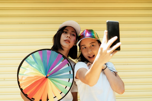 Selfie of lesbian couple infront of yellow rolling steel door with a colorful wheel.