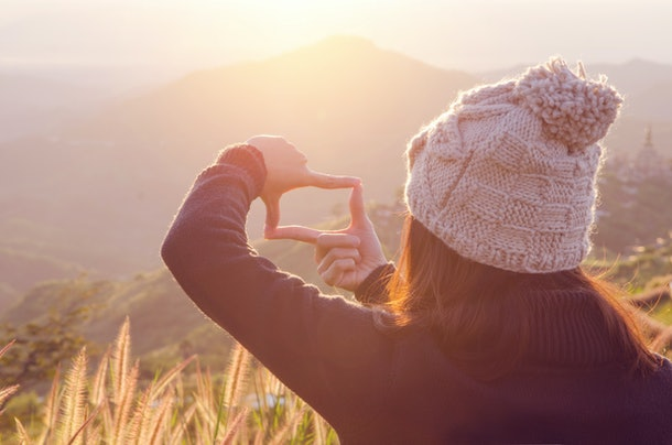Close up of woman hands making frame gesture with sunrise on moutain and field, Female capturing the sunrise, Future planning, sunlight outdoor.