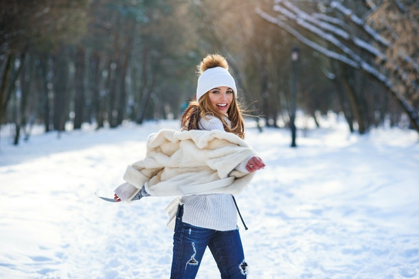 Beautiful young woman having fun and dancing in winter snowy park.