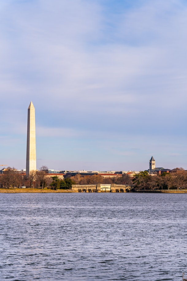 The Washington Monument in Washington D.C. stands against a purple-blue sky on a winter day.