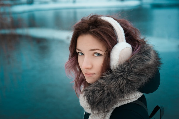 girl with red hair in a dark winter jacket and hood with fur in fur pink headphones in the park against the backdrop of the lake