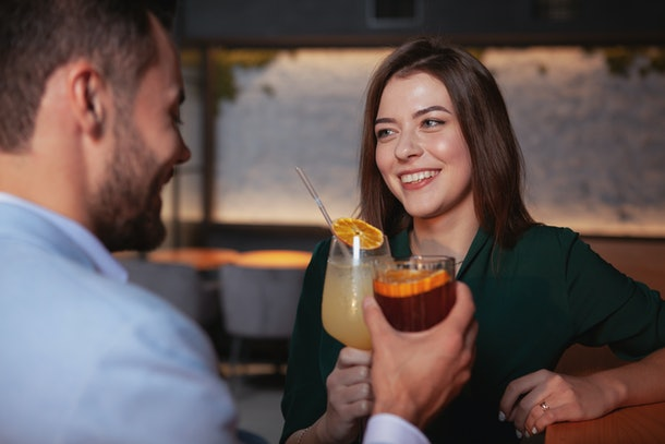 Beautiful cheerful woman enjoying night out with her boyfriend at cocktail bar. Couple celebrating anniversary