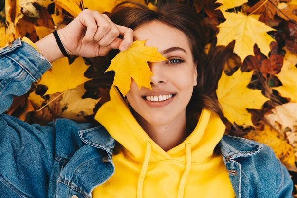 Autumn walk. Woman portrait. Happy girl in yellow hoodie and jean jacket is playing with leaf, looking at camera and smiling while lying on the ground in the park; top view