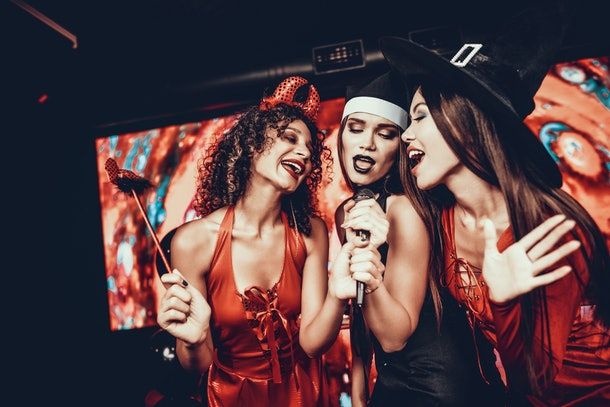 Young Women in Halloween Costumes Singing Karaoke. Happy Smiling Friends Wearing Costumes having Fun by Singing with Microphone at Halloween Party in Nightclub. Celebration of Halloween