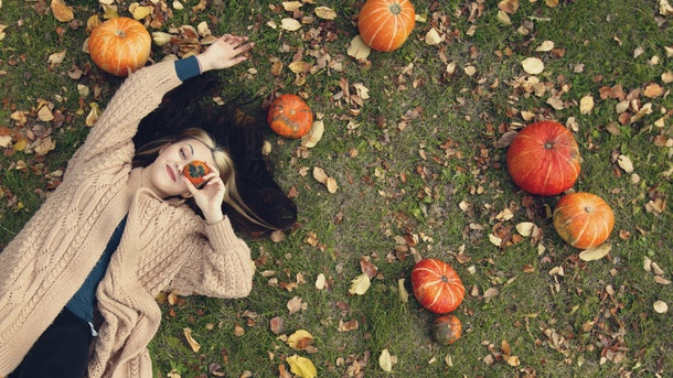 A beautiful woman is lying on the grass. Top view. She lies near the pumpkins. She holds a small decorative pumpkin near her eye.