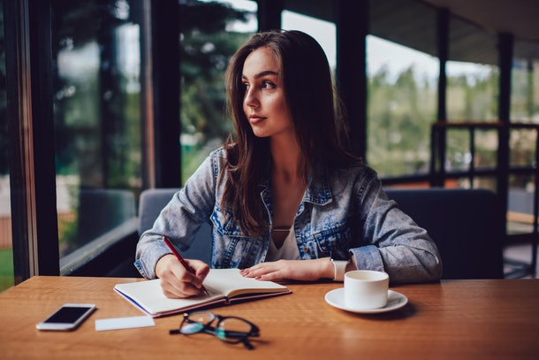 Thoughtful skilled author looking out of window and thinking on writing interesting essay for preparing for seminar sitting at table with pen in hand and cup of tasty coffee in stylish cafeteria
