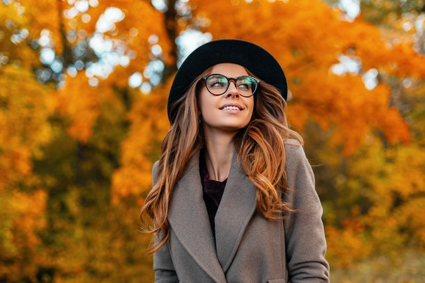 Pretty young elegant woman model in a luxurious hat with glasses in a coat with a beautiful smile walks in a park among a tree with orange foliage. Modern cheerful girl hipster posing in the forest.