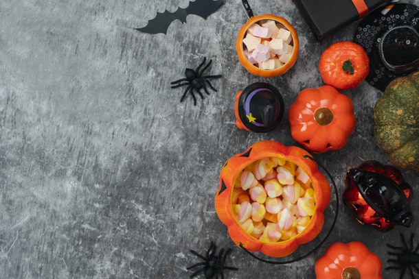 Table top view aerial image of decoration Happy Halloween day background concept.Flat lay accessories essential object to party athe pumpkin & sweet candy on rustic stone.Space for creative design.