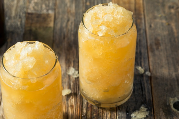 Two apple cider slushies sit in large glasses on a wooden picnic table.