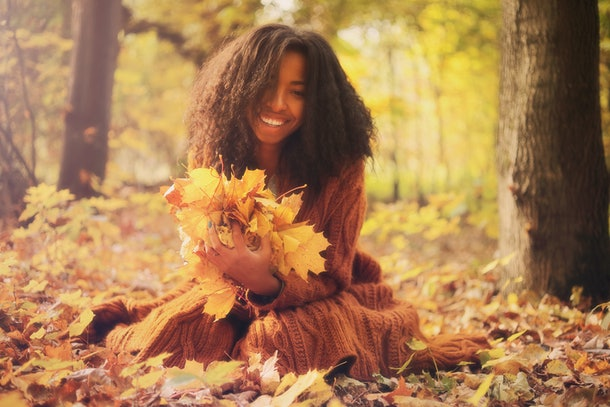 Young black woman with autumn leaves in hands relaxing in the autumn forest on a sunny day.