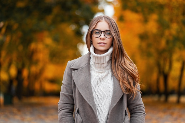 Autumn portrait of an attractive young woman in stylish glasses in a knitted fashionable white sweater in an elegant coat in a park on a background of trees with orange leaves.Girl walks in the forest
