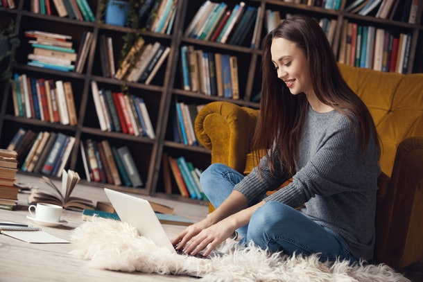 Young woman writer in library at home creative occupation sitting typing on laptop