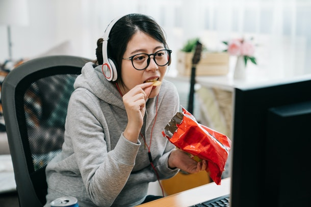 funny young asian woman otaku sit at home with pack of snacks in his hands eating chips and watching videos on computer screen. female student on summer break binge watch on internet with junk food.