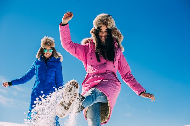 Two girlfriends have fun and enjoy the fresh snow on a beautiful winter day in the mountains