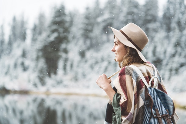 Beautiful young woman spending time in front of incredible mountain lake. Wearing hat, poncho and backpack. Winter is coming, first snowfall. Wanderlust and boho style