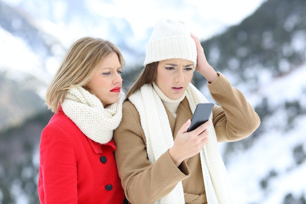 Two confused friends with a smart phone in winter on holidays in a snowy mountain