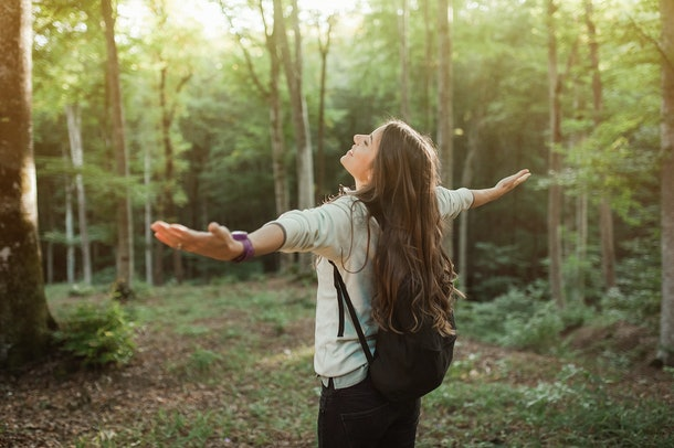 Young woman emgracing the sun and nature with backpack in the forest on sunset light in the autumn season, looking up, exploring the nature.