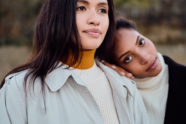 Portrait of attractive African American girl intently looking in camera standing with pretty Asian friend outdoor