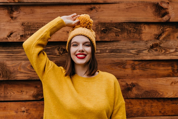 Smiling amazing woman touching her yellow hat. Photo of refined european girl with red lipstick standing on wooden background.