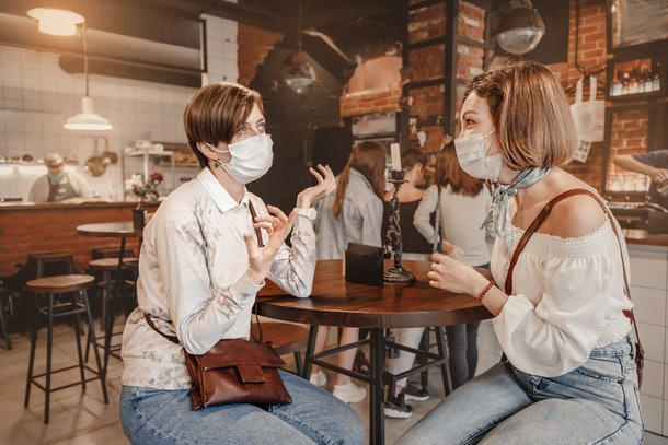 Friends girls met in a cafe and communicate with each other and chat. Wear medical protective masks. An outbreak of the coronavirus epidemic. New rules for social distance and isolation