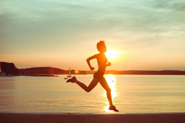 Attractive young African girl athlete running at sunset or sunrise along the beach