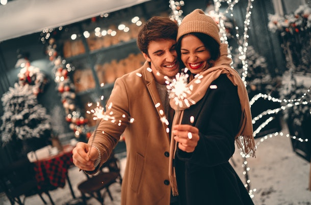 Young romantic couple having fun outdoors in winter before Christmas with sparklers in hands.Enjoying spending time together in New Year Eve.Two lovers are hugging and kissing in Saint Valentine's day
