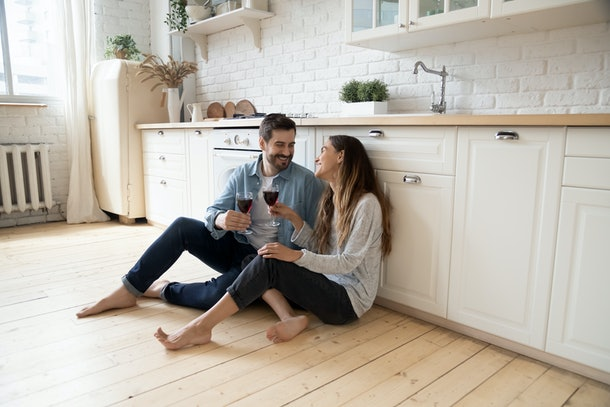 Romantic smiling couple young guy and girl sit on warm kitchen floor talking holding glasses having fun together, happy friendly husband and wife laughing enjoying drinking red wine at modern home