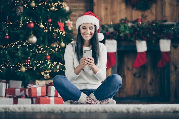 En casa, la chica positiva con decoraciones X-Mass usa un sombrero de Papá Noel con descuento de Navidad en busca de sus mensajes de texto tipo teléfono inteligente en la cómoda alfombra del piso.