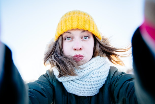 Portrait of young  woman in knitted yellow cap, scarf and mittens taking selfie and heaving fun in winter day.Fitness girl enjoying sunny winter day.Lifestyle happiness emotions nature on background.