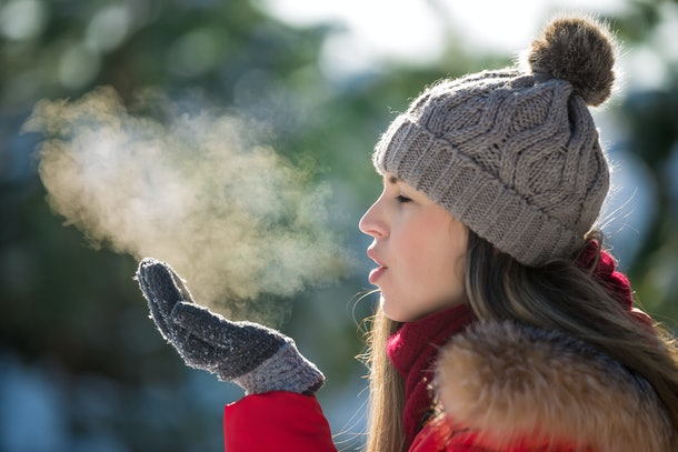 Attractive young woman breathe out steam outdoor in winter