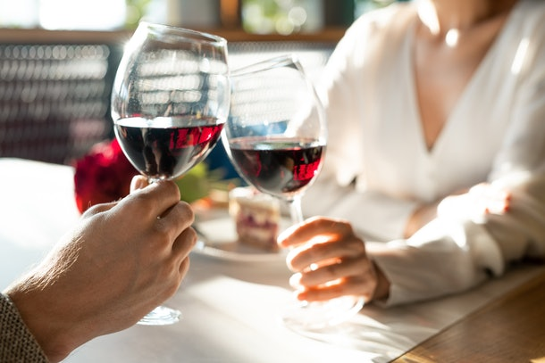 Hands of young man and his girlfriend clinking with wineglasses over table while enjoying romantic date and lunch in luxurious restaurant