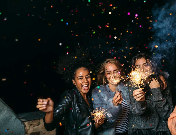 Group of happy friends celebrating new year's eve with confetti and sparklers