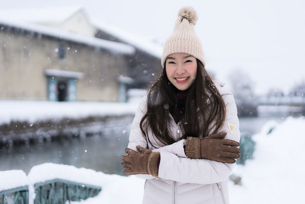 Beautiful young asian woman smile and happy with travel trip at Otaru canal Hokkaido Japan in Snow and Winter Season