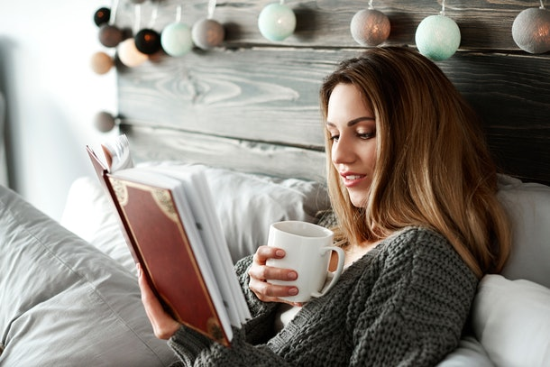 Woman drinking coffee and reading book on bed