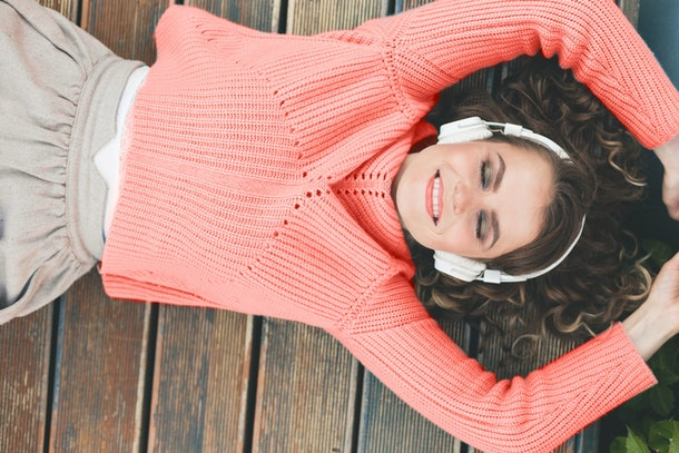 woman in fashionable clothes, in a sweater of the color of the year 2019 living coral, in headphones. lifestyle