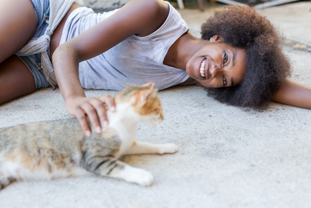 Beautiful afro american woman with her cat on the terrace. Concept of spending time with our pets and relax time.