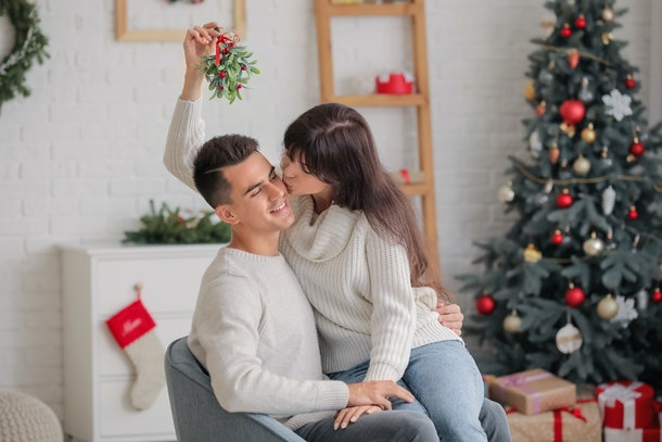 Young woman kissing her husband under mistletoe branch at home on Christmas eve
