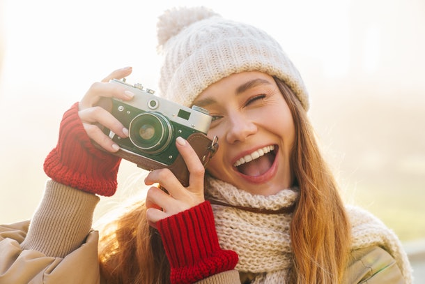 Close up of a cheerful pretty young girl wearing winter jacket and a hat standing on a city street, holding photo camera