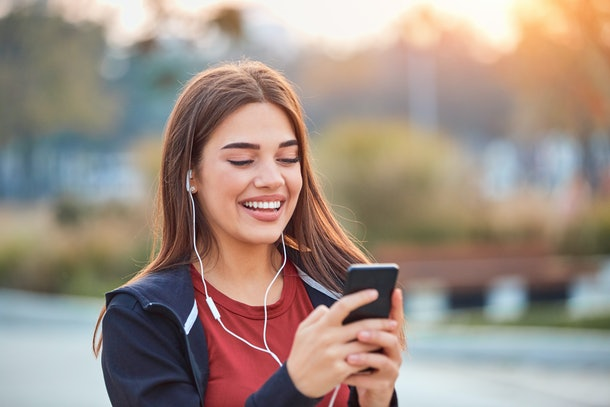 Modern young woman with cellphone making pause during jogging / exercise.