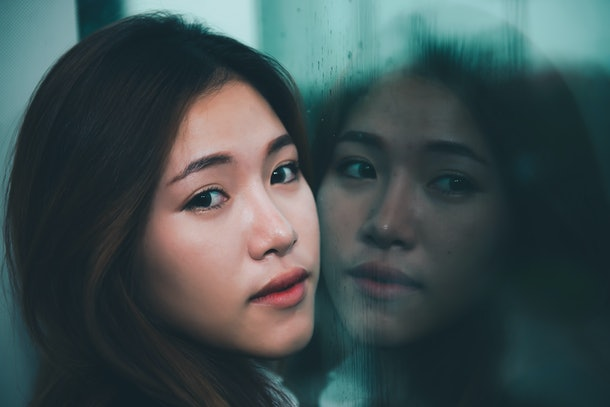 Closeup asian sad woman at mirror with reflection in a raining day vintage style,heartbreak woman concept,stress girl