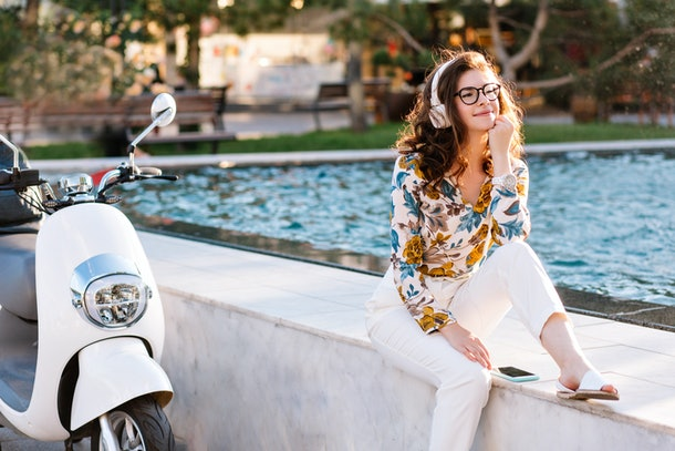 Dreamy girl with elegant hairstyle listening music and looking away, spending time near fountain. Amazing young lady in glasses and big white earphones chilling outdoor after riding on scooter.