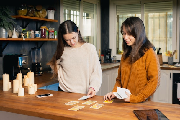 Two young females: One in cream jersey and the other in a tan jersey playing tarot cards in the kitchen of their home. Tablets and mobile phones are visible in the shot as well as candles