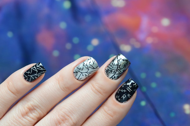 A woman's nails are painted black and silver, with various constellation and zodiac symbols on them.