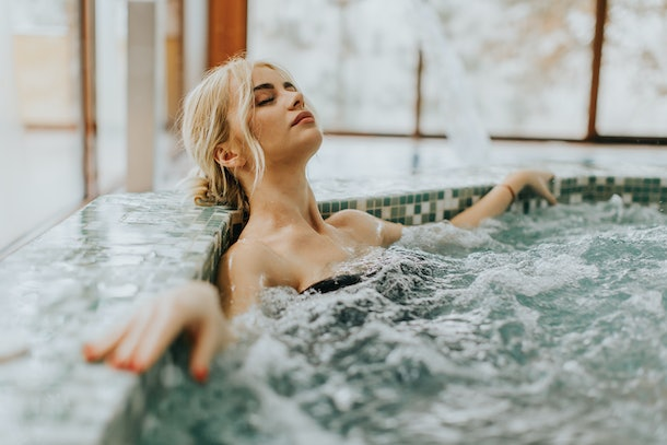 Pretty young woman relaxing in the whirlpool bathtub