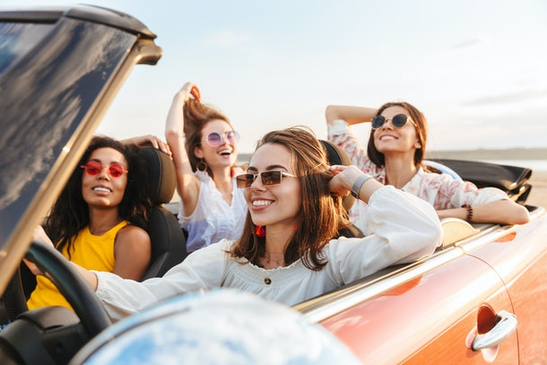 Photo of a beautiful gorgeous smiling cheery young pretty women friends driving the car.