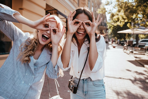 Lovely girl with blonde hair chilling outdoor with friend. Photo of brunette lady having fun with sister on the street.