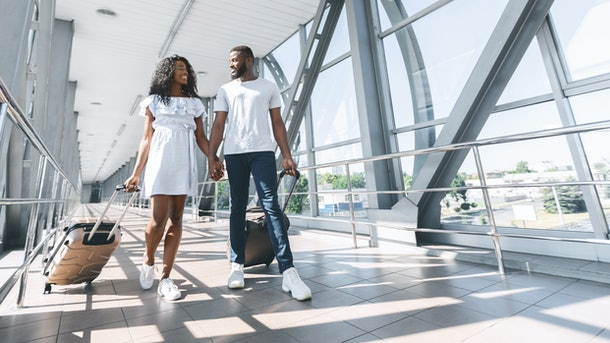 A happy couple smiles at each other and holds hands while walking through the airport with their suitcases on a sunny day.