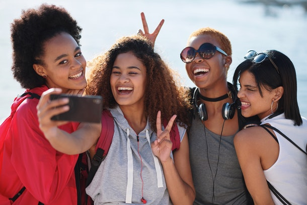 Female friends smile and pose for a selfie on a sunny afternoon.