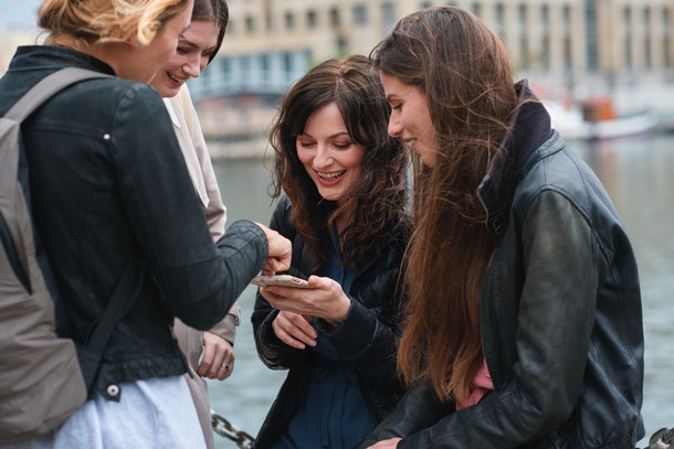 A group of friends chill on a bridge and look down at a cellphone.